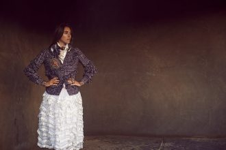 Multi-coloured tweed jacket, white organza skirt, multi-coloured scarf, gold and red brooch, bracelets and ring, CHANEL