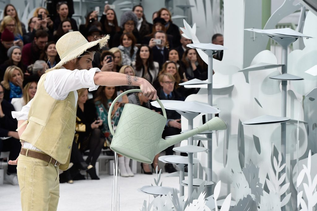 Baptiste waters the origami flowers and brings the Chanel world into colour (Photo by Pascal Le Segretain/Getty Images)