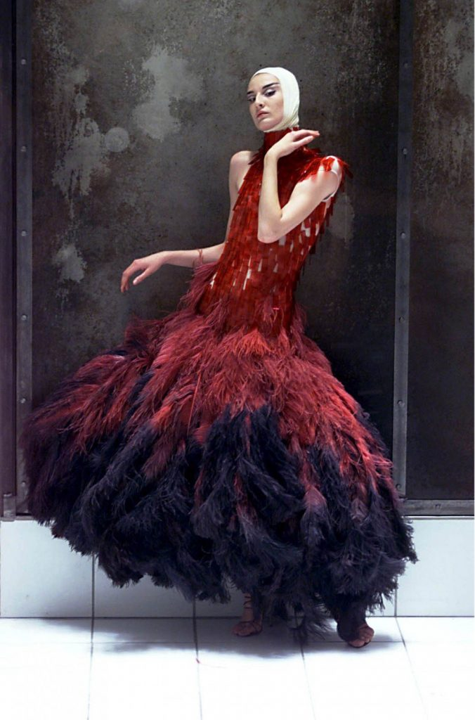 Model Erin O'Connor wearing dress of dyed ostrich feathers and hand-painted microscopic slides, photographed by Rex