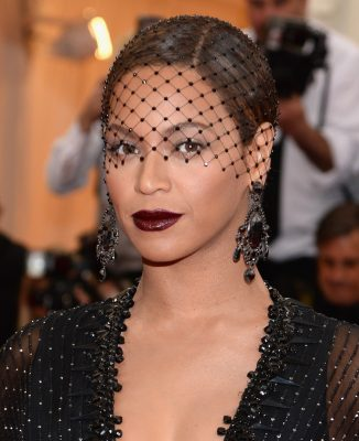 Beyoncé wore a black cherry lip and ebony birdcage veil, matched with statement chandelier earrings and a minimalist chignon when she attended the Charles James: Beyond Fashion Costume Institute Gala in New York.