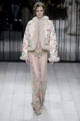 Emma Harris struts down the runway in a sheer, jewel-mottled Alexander McQueen lace dress, worn with an opulent nude pink floral and butterfly-embroidered jacket with plush fur trim.