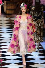 At Milan Fashion Week, Dolce & Gabanna's duster coat boasts a variety of chunky fuchsia flowers, as if freshly plucked from an English rose garden. Underneath lays a sheer silk and satin baby pink evening dress.