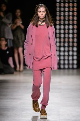 Vivienne Westwood goes bold with an explosion of mauve and pink. Here wide trousers are matched with a thin jumper and cosy cardigan of the same, rosé-tinted shade. Partner with some funky platform sneakers for a real statement look.