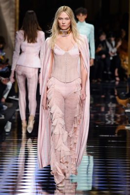 A rose-smothered Karlie Kloss is pictured here in a seductive leather bustier, worn with slim, plisse trousers that are adorned with fluttering feathers. A sweeping duster coat perfects an already striking outfit.