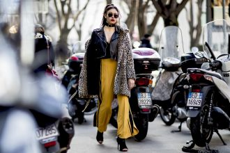Mustard yellow flared trousers and a leopard print coat make a bold statement