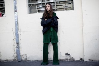 A black puffer jacket worn off the shoulder provides a visual break from head-to-toe metallic green lurex.