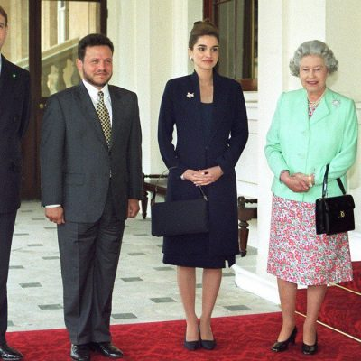 When: May 1999 | Looking the epitome of elegance, Queen Rania stands between her husband and Queen Elizabeth during a state visit to Buckingham Palace, London, in a navy suit and matching kitten heels, which she wears with an understated black, structured bag.