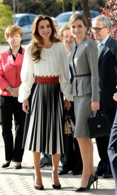 November 2015 | During a visit to see her friend, Queen Letizia of Spain, a balloon-sleeved white top with a high-neckline is given an ultra-feminine silhouette thanks to a maroon-hued belt, which accessorizes a black-and-white mid-length silk skirt.