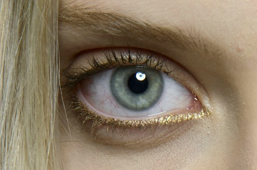 The Eye | Long-lasting glitter shadow can completely elevate one's look, as seen here on an Alexis Mabille model. This natural, pared back eye is brightened with subtle glittering gold eyeliner, which is generously applied on the bottom lashes.