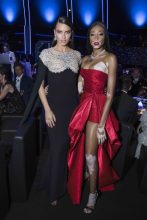 Looking breathtakingly beautiful, supermodels Adriana Lima and Winnie Harlow pose at Chopard's Space Party in dramatic jet-black and plush ruby-red sweetheart gowns.