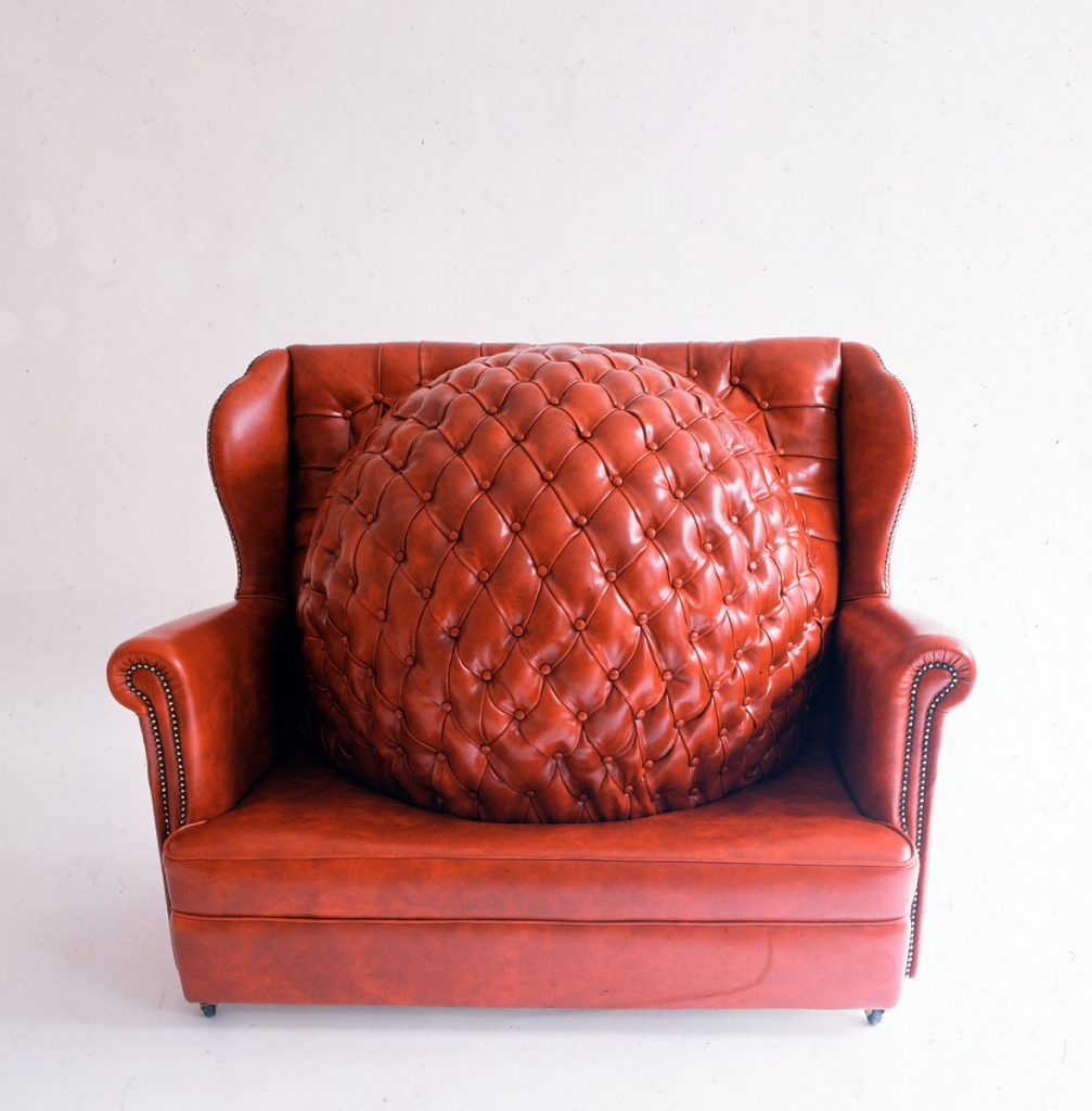 This red leatherette Chesterfield style chair is one of Saunders's most popular works. The Age Of Reason, 1995, 98 x 126 x 82cm