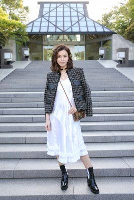 Hong Kong actress Janice Man draped a tweed and leather jacket over a tiered slip dress. A choker and patent leather boots finished the look