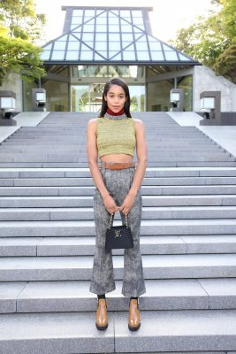 American actress Laura Harrier donned a cropped sleeveless turtleneck with high-waisted trousers in pared-back shades of olive green and grey.