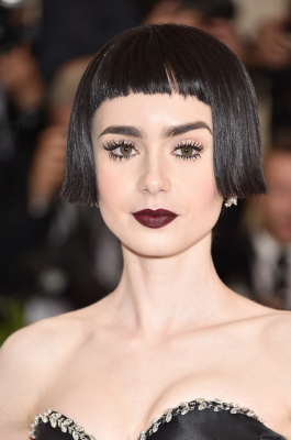 Lily Collins. Everyone needs a film noir moment. Take cues from Lilly Collins and apply Lancôme Le Crayon Khol in black ebony, before layering Lancôme L'Absolu Rouge in 397 berry noir on top. The combination seeps delicately into lips and gives you gothic romanticism for days. Her hairstyle was a remarkably realistic wig cut in perfect precision.