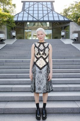 Michelle Williams looked polished and demure in a sleeveless mixed print dress high shine boots added an element of punk.