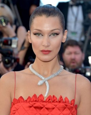 Bella Hadid emphasised her extreme feline flicked eyes with a sleek, pulled back ponytail. A light dusting of red eyeshadow and translucent lipstick completed the look.