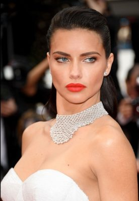 Brazilian beauty Adriana Lima opted for a vibrant pop of orange lipstick to liven up her white gown. Slicked-back wet look hair added further glamour.