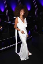 27-year-old model Tina Kunakey looks truly stunning in an alabaster plunging floor-length gown that perfectly complements her slim frame.