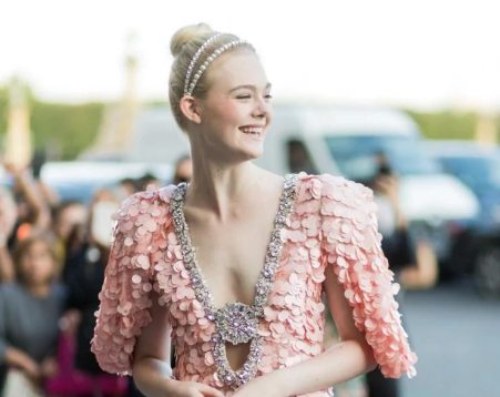 Elle Fanning. Opting for a simple brush of blush across the pout and a delicate matte-pink lip, the actress's hair was brushed back with two polished bands of pearl when attending the Miu Miu cruise show during Couture Week. While the undertones of pink and Fanning's skin tone could very well have resulted in a 'faux-pas', minimal application of the colour tone across the face and matching the sheen of the dress contributes greatly towards this effortless result. Try the Rouge Dior balm in soft peach.