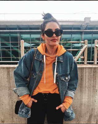 Middle Eastern influencer Karen Wazen Bakhazi throws shade in a bright orange sweater, oversized sunnies and a messy top knot to complete. A bold lip and brow keeps her look glamorous.