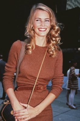 1992: Schiffer wears a cinnamon-hued knitted dress and shoulder bag, while simultaneously sporting a head of golden tightly wound curls.