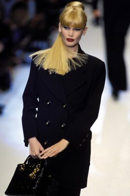 1994: On the runway, a heavy-fringed Schiffer turns heads in an extraordinarily modern ensemble on behalf of Christian Dior, worn with ruby-red lips and a dramatic cateye.