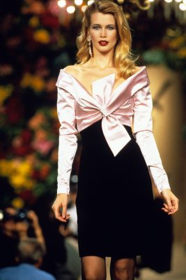 1996: Pretty in pink – Schiffer stalks the runway for Yves Saint Laurent in a figure-fitting dress, which features a jet-black pencil skirt, which is superbly paired with a glossy shirt-like top.