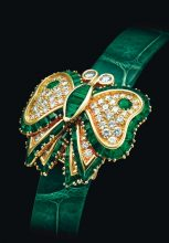 This emerald and diamond watch by Audemars Piguet was sold at Christie's Auction House. The circular green engine-turned dial is concealed under a butterfly cover that's smothered in circular-cut diamonds. The piece is further lined by baguette and whistle-cut emeralds and accented by circular-cut emeralds.