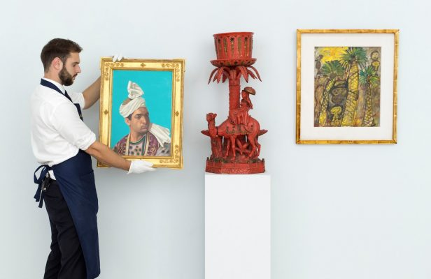 At Sotherby's Dubai, DIFC, a man hangs paintings in preparation for the exhibit.