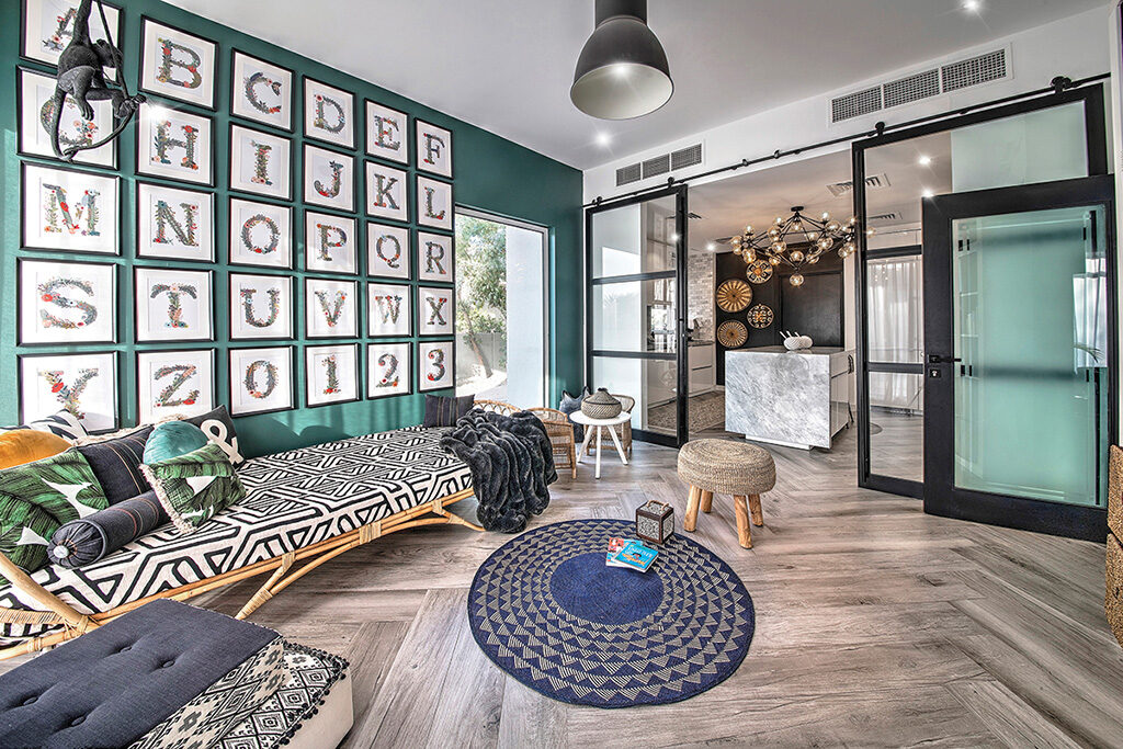 One of Carla's favourite rooms in the house, the playroom, benefits from a pop of hunter green on the wall, with banana leaf print cushions and cane furnishings
