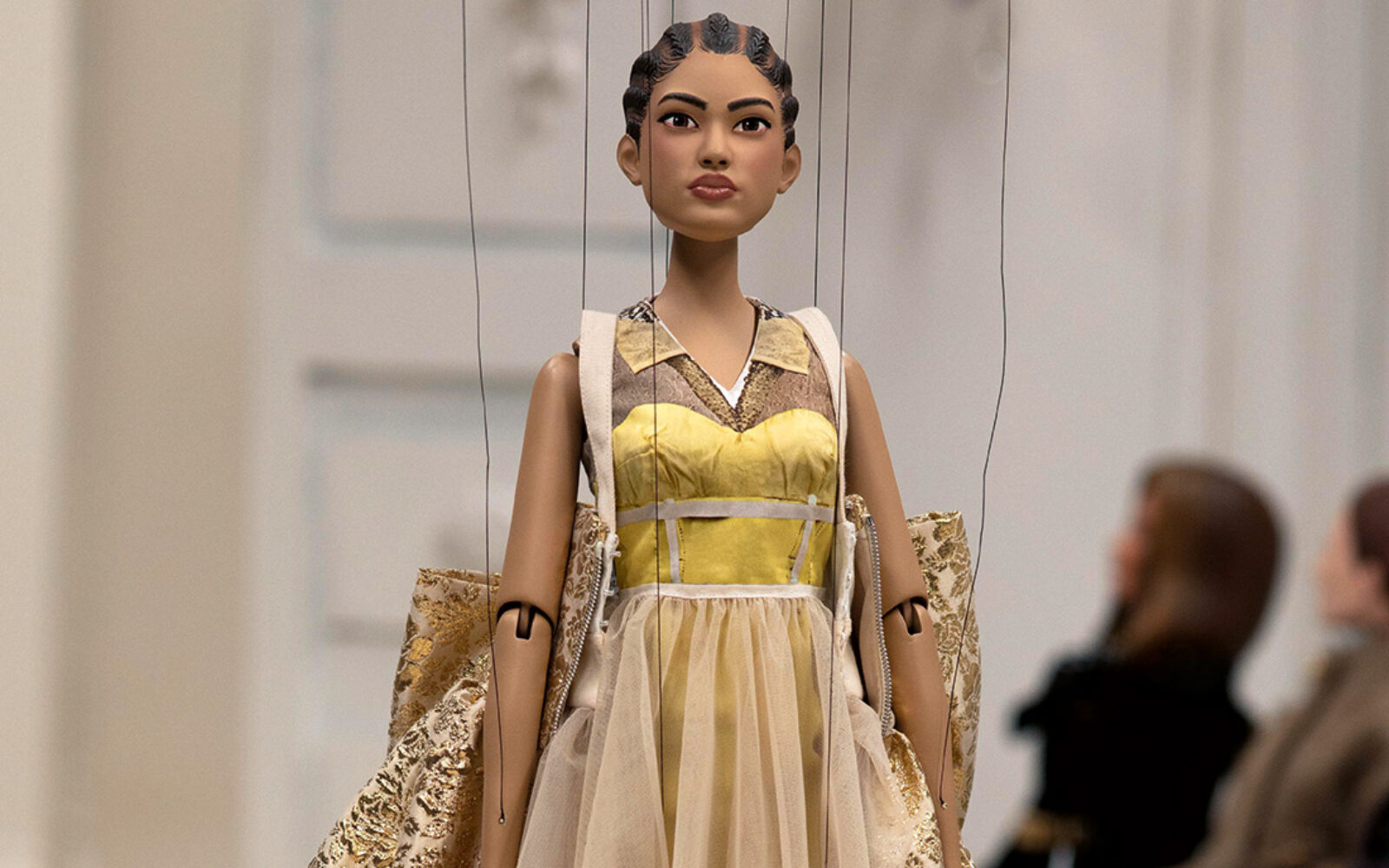 A doll walks the Moschino runway in place of models, wearing a gold dress