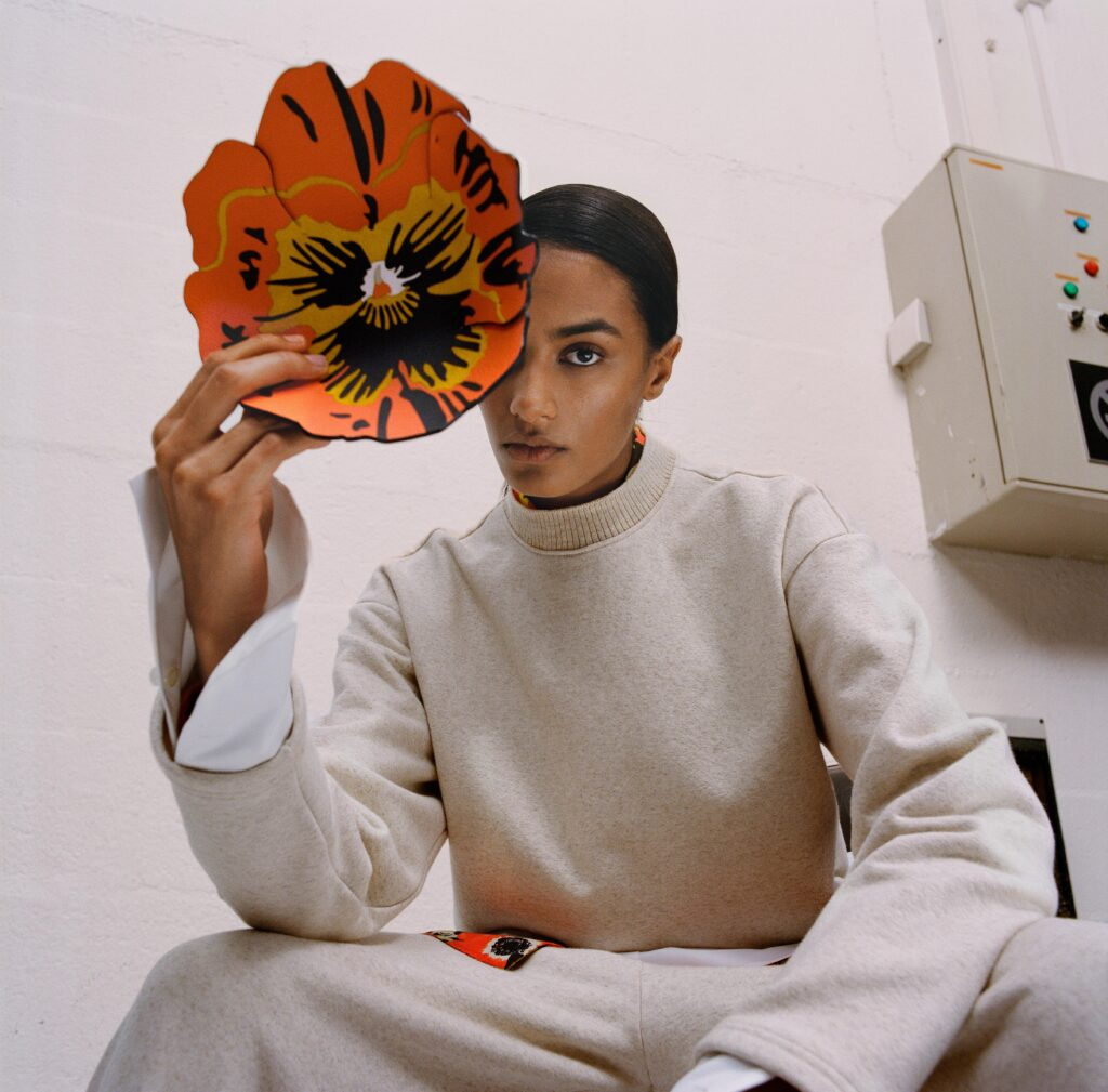 The Biggest Trends Of Pre-Fall 2021, Model wears beige Loewe sweatsuit and holds a flower in front of her face