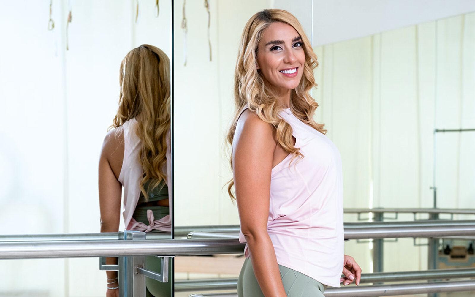 Goli Hashtroudi Cramer poses in front of a mirror in a fitness studio