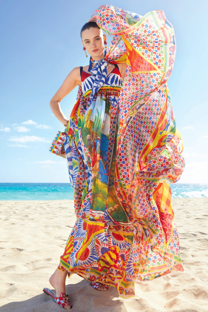 The Biggest Trends Of Pre-Fall 2021, Model stands on the beach wearing a colourful dress by Dolce and Gabbana