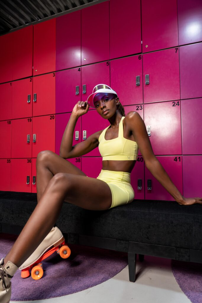 L'Couture Energy Will Get You Excited About Going To The Gym; Woman wears the lime set, sitting in a locker room