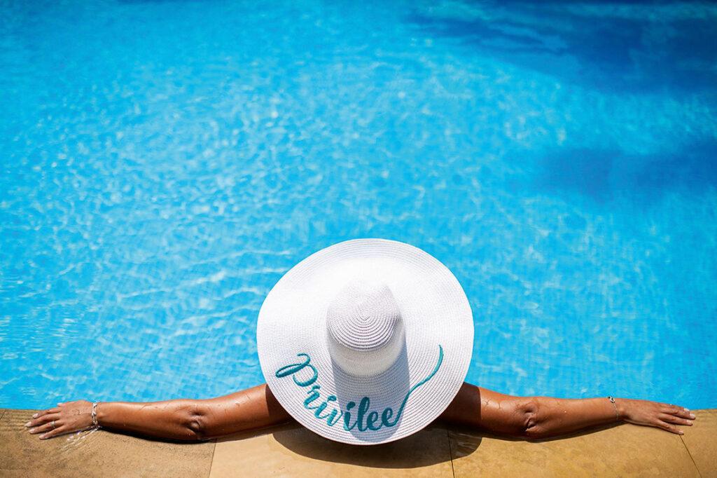 Person poolside wearing a Privilee hat