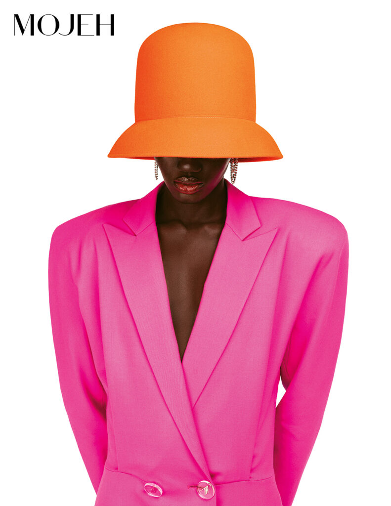 Model wears orange Nina Ricci hat covering her eyes, The Attico pink blazer and coral lipstick