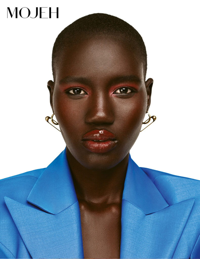Model in blue blazer wears coral eyeshadow and red lip gloss