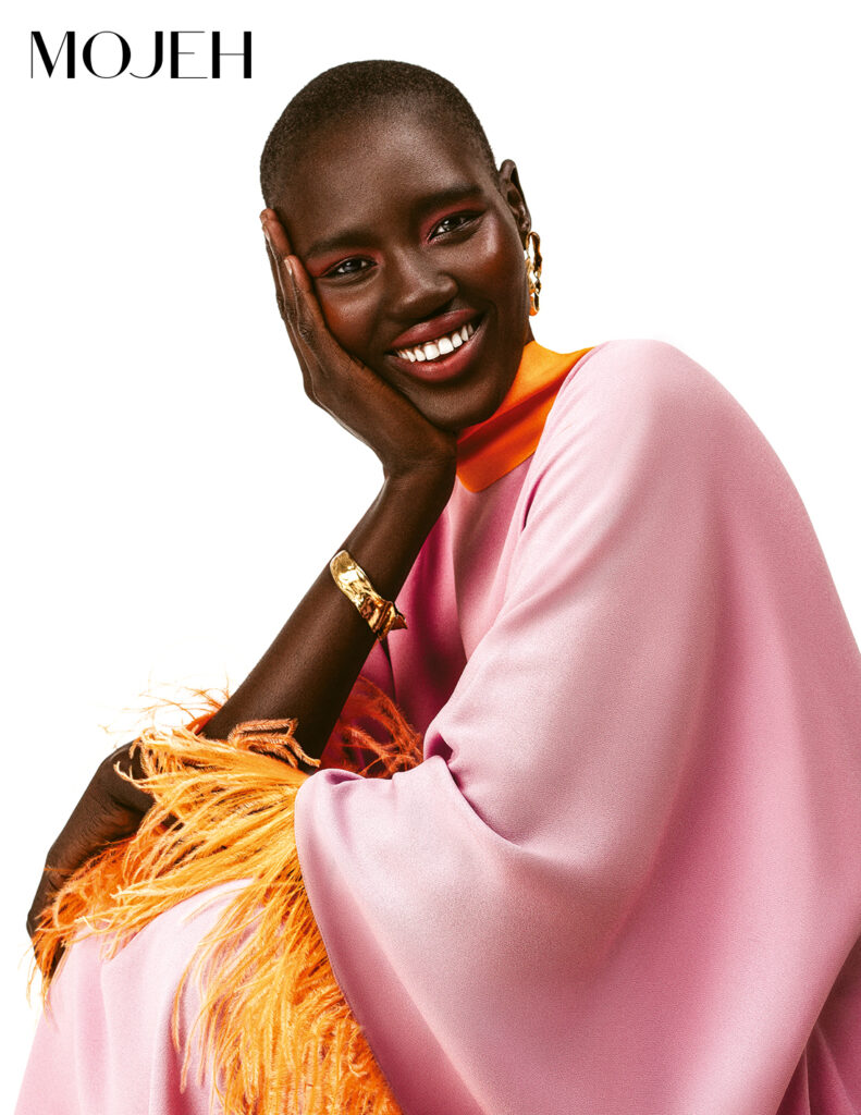 Model wears pink and orange cape, coral makeup, and smiles at the camera