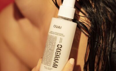 Model holds Ouai x Byredo Leave-In Conditioner