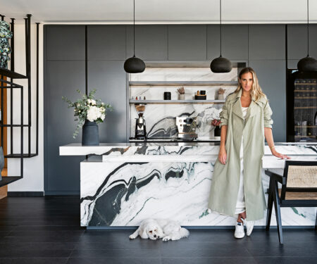 Sally Matthews, wearing a khaki coat, stands in front of her marble kitchen island.