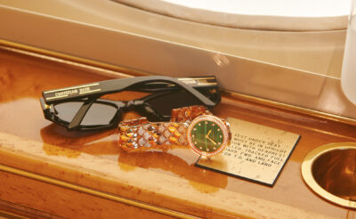 Travel watch; Rolex and Dior sunglasses on the armrest of a private jet