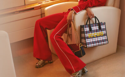 Travel Accessories You Can't Be Without This Holiday. Model wears handbag, shoes and pantsuit, all Gucci.